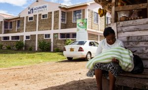 A mother with her newborn child in front of the Ruiru maternity clinic.